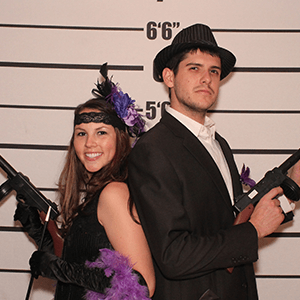 Grand Rapids Murder Mystery party guests pose for mugshots